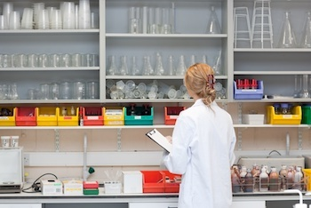 Serious female scientist writing on her clipboard in a laboratory-2